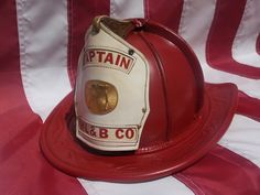 "here's an unusual Salamander ""Captain"" officer's fire helmet... 1960's ? Cairn's & Bros. New Yorker model helmet. It boasts a large center brass badge of two axes to designate it as a Captain's helmet. Rear rib panels are painted/restored in white to designate as Company Officer."