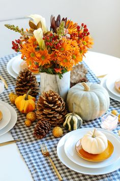Add some simple country charm to your Thanksgiving table with a blue and white gingham table runner accessorized with pinecones, white pumpkins, gourds, and the Julia centerpiece, $40, by UrbanStems.    - CountryLiving.com