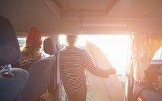 Stock Photo : Surfing couple look out to sea from camper van.