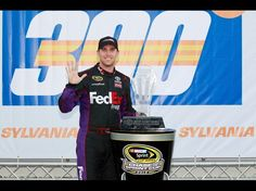 Denny Hamlin, driver of the #11 FedEx Freight Toyota, poses with the trophy in Victory Lane after winning the NASCAR Sprint Cup Series SYLVANIA 300 at New Hampshire Motor Speedway on September 23, 2012 in Loudon, New Hampshire.