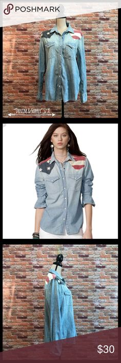 "Denim & Supply Ralph Lauren Flag Chambray Shirt Denim & Supply Ralph Lauren Flag Chambray Shirt in a size XL.  Has two front flap closure pockets with snaps. Button at top of collar and then six white enamel snaps.  One enamel snap on each front pocket and three on each cuff, plus one button on each cuff.  Flag appliqué on shoulders and across the back.  Rounded hem.  Measures approximately 22"" armpit to armpit and 27"" in length.  100% cotton.  In excellent condition. Denim & Supply Ralph…"