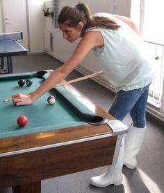 Amateur playing pool in jeans and white wellies