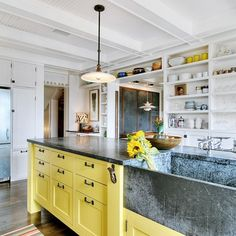 """utilitarian yellow and white kitchen cabinets with soapstone apron front sink."" Those cabinets.  They're awesome."