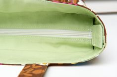 This site has some good calculations for how to cut your out & inner fabric if you're going to do a recessed zipper in a tote bag.  She attaches the zipper tabs to the bag.