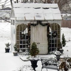 Little greenhouse decorated for Christmas... Looks like there are even drapes inside... If there is electricity for a space heater this would be a lovely little spot for a small luncheon.