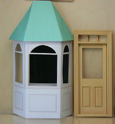 A printable bay shop window shown next to a dolls house door for scale.