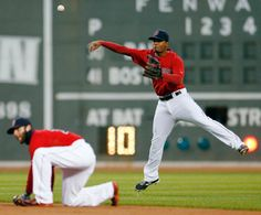 Boston Red Sox's Xander Bogaerts (2) throws over teammate Dustin Pedroia (15) on a single by Baltimore Orioles Adam Jones in the first innin...