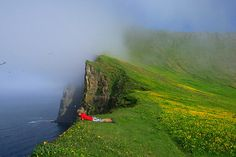 A hiker peers over sea cliffs Iceland. Image by Johnathan Ampersand Esper / Aurora / Getty Images