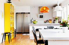 pops of color in white kitchen, Kartell and Muuto pendants