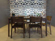 Sala de jantar mesa de madeira e cadeiras de madeira, parede cinza.