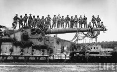US soldiers posing standing on barrel of captured german rail gun