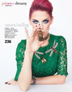 Wearing a green lace dress from Dolce & Gabbana, Ashley Smith poses with insect brooches