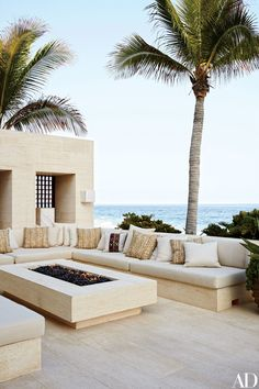 In Cindy Crawford and Rande Gerber's Mexican villa by Legoretta + Legoretta, the outdoor living room's seating, made of niwala limestone from Spain, is topped by cushions clad in a Ralph Lauren Home fabric.
