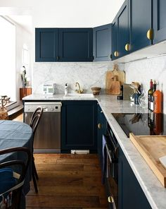 Julie, Paris apartment kitchen--dark teal cabinets, wide plank wood floors, modern brass hardware, Carrara marble slab counters and backsplash. Modern with a nod to the past. Two Tone Kitchen Cabinets, Kitchen Countertops, Teal Cabinets, Kitchen Decor, Kitchen Design, Kitchen Ideas, Kitchen Wood, Kitchen Tips, Parisian Kitchen
