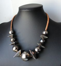 1980s Italian designer Wilma Spagli statement necklace composed of alternating graduated silvertone metal square and round shaped beads mounted on a tan leather cord. The modern geometrical choker necklace was made in Italy, in the eighties. There is a large Spagli typical lobster claw clasp with the signature of the Italian designer. The necklace in excellent vintage condition with normal wear on the leather cord and nice dark patina. Circa: 1980  Provenance: Italy  Designer: Wilma Spagli…