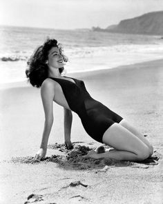 circa 1945: Actress Ava Gardner (1922 - 1990) poses on the beach in a one-piece swimsuit.