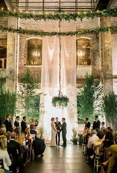 15 Gorgeous Indoor Wedding Backdrops To Try: an ethereal curtain, lots of greenery around and greenery chandliers completely change the industrial venue