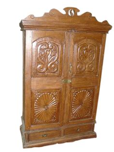 "Antique chakra carved teak wood cabinet/armoire India cabinet.  This cabinet has two doors that fold to the sides and drawers that add to its practicality.Eclectic addition to your interiors .  Scalloped arch carved at top of the cabinet.  The crown molding adds a classic touch.  Hand carved rustic wood armoire are uniquely designed and handcrafted with such warmth that they add a beautiful dimension to your interiors.  Exterior Dimensions : Height 66"" x Width 37"" x Depth 16""(add 3 inches…"
