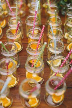 jars with orange wedges and colorful straws, photo by Lara Hotz http://ruffledblog.com/sydney-polo-club-wedding #weddingideas #drinks