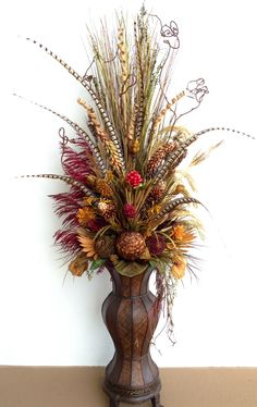 Six feet tall dried floral arrangement with pheasant feathers. By Arcadia Floral & Home Decor