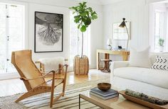 Organic-modern living room with a striped kilim rug, fiddle leaf fig tree in a braided basket, white sofa and white African mud cloth accent pillows.