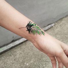 Fern frond tattoo on wrist by Zihee
