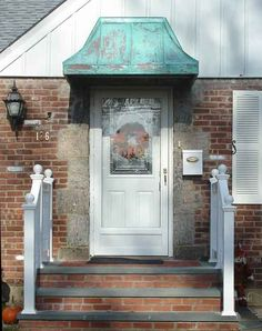 Concave copper door awning with patina