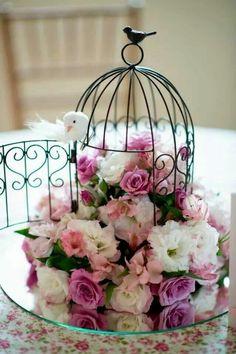 Centro de mesa com gaiola e flores