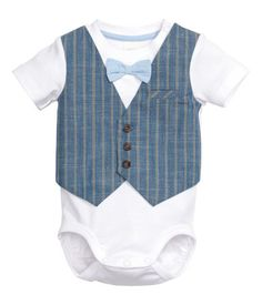 Short-sleeved bodysuit in soft ribbed cotton jersey layered with a vest front in woven fabric with buttons and a decorative chest pocket. Attached bow tie at neck and snap fasteners on one shoulder and at gusset.