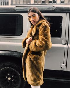 Faux fur coat and yellow aviator sunglasses