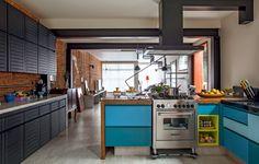 No projeto do escritório Casa 14, a bancada de madeira, da Madeira de Demolição, separa a cozinha da sala de jantar. O armário ganhou diferentes tons de azul nas portas e um nicho amarel. Ao lado, o armário antigo com tinta preta é um discreto coadjuvante