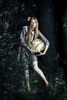 In this photo, Alice is sitting down at the end of the rabbit hole (after falling through it), looking up at the various different-sized clocks above her head (a reference to the White Rabbit). Description from pinterest.com. I searched for this on bing.com/images