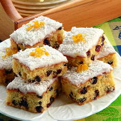 A soft, cake-like slice generously filled with currants and topped with lemon icing and coconut.