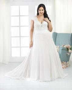 1800 - Beaded Alencon lace covers the bodice of this natural waist plus size gown, Scalloped lace appliqués encircle the V neckline and back as well as the cap sleeves. The full A line skirt is topped by a rushed chiffon band. Clear rhinestone buttons and floral beading extends down the train.