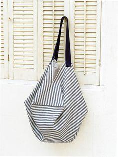 ユニークな形の大きなバッグは四角形の布地一枚を縫い合わせて持ち手をつけただけ。 たっぷり荷物が入るのが嬉しい。 夏にぴったりのストライプ模様です。