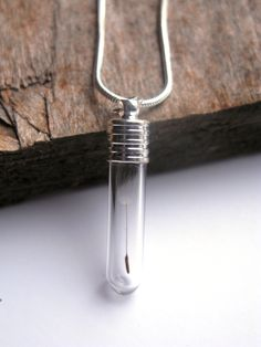 Suspended in a tiny glass vial is a real tiny dandelion seed. The silver tone cap is securely attached and the pendant hangs from an 18 silver plated snake chain. I could change the chain to a longer flat link chain or switch it for a leather cord if you prefer. There is no resin in this particular pendant.  The pendant measures 1 1/4 tall (32mm) by 1/4 wide (7mm). It is a tiny pendant!  See all my other Dandelion items here: http://www.etsy.com/shop/ScrappinCop&...