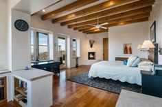 Southwestern Master Bedroom with Cement fireplace, High ceiling, Exposed beam, Armstrong Whisper Harvest Hickory, Carpet