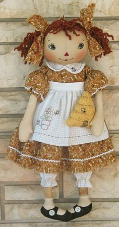 charming rag doll holding a bee skep