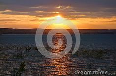 A classic sunset image of a high golden sun exiting a cloudy sky to reveal a bright radiant sun radiating and reflecting across the waters of Wilson Lake Reservoir. Sunset Images, Golden Sun, Classic Image, Sunrises, Around The Worlds, Bright, Sky, Water, Outdoor