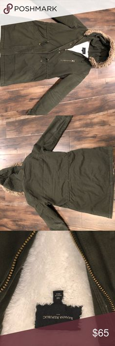 Banana Republic Olive Green Faux Fur Parka Gently worn.  White fleece lining.  Zippered outside pocket on upper left.  Two hand pockets.  Drawstrings in the waist.  Snaps on the wrists.  Detachable faux fur lined hood.  Machine washable. Banana Republic Jackets & Coats Utility Jackets