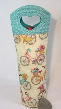 Pastel Bicycles with Baskets Full of Flowers on a Soft Yellow Background! Such a sweet fabric I couldnt resist it!!  This wine bag is a perfect fit for a 750ml bottle of yummy summer wine....give it as a hostess gift OR keep it for yourself!  This FUN fabric is teamed with soft teal flowers, fully quilted with lots of fun wavy lines and finished off with a spiral - quilted round bottom for a perfect fit !  ALL MY BAGS ARE: *fully quilted *completely lined *round fitted bottoms *Inside seams…