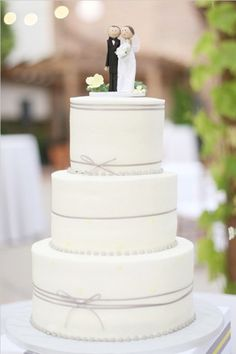 White tiered wedding cake decorated with thin bows  #cake #wedding #white #bow #simple