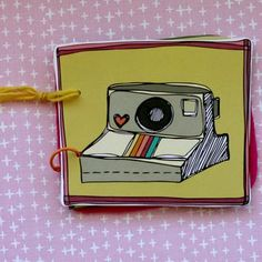 mini album for polaroid pictures with a drawing of a polaroid camera on the front.