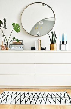 Love this modern six-drawer credenza, styled with fresh green plants, pops of brass and ceramic, and modern black accents on top, below the round gold-edged mirror, and above the geometric black and white runner rug below.