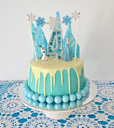 Frozen inspired Birthday Cake. Layers of chocolate cake with vanilla buttercream. Decorated with white chocolate shards, white chocolate ganache drip, glittery snowflake bunting garland, Frozen figures and a DIY gem candle.