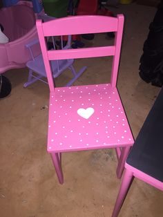 Chair spray paint makeover. Pink spray paint all over a wooden children's chair and white polka dots in acrylic paint.