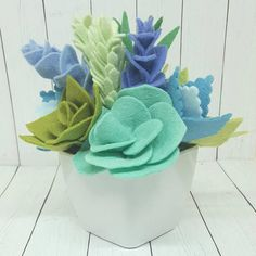Felt succulent and flower arrangement in a white container. Planter is approximately 3 inches square, and finished arrangement is approximately 5.5 inches tall. Felt succulents in pistachio, julep, fern, seafoam, geranium, mint, sky, periwinkle, salt water adnd icicle. All the