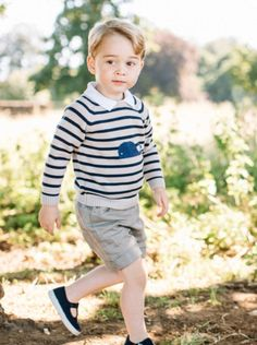 Dressed in a striped jumper, Prince George looks cherubic as he poses in newly released ph...