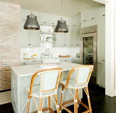 All white kitchen with wooden accents with an island used for dining