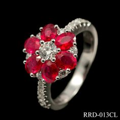 Breathtaking ruby and diamond cluster ring in 18ct white gold. Comprising of 1.80ct oval cut rubies set in a flower formation and combined with .57ct round cut diamonds this is a fabulous piece of jewellery. The delicate diamond set band puts emphasis on the stones creating a stunning design that is sure to be a talking point. £3800